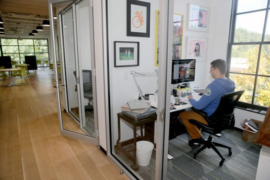 Nick Johnson of Cima Creative rents a working space a the Vibe Coworks in Poulsbo. He designed the logos for the shops.
