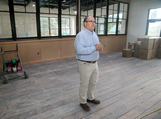 """Dan Ryan, president of Tim Ryan Construction, stands on a recycled wood floor, made from pieces of an old barn in Keyport, at the new Centennial building in Poulsbo. The building will soon be home to Vibe Coworks (coworking space), ChocMo (restaurant), High Spirits (""""destination"""" liquor store) and Crabtree Kitchen + Bar (restaurant)."""