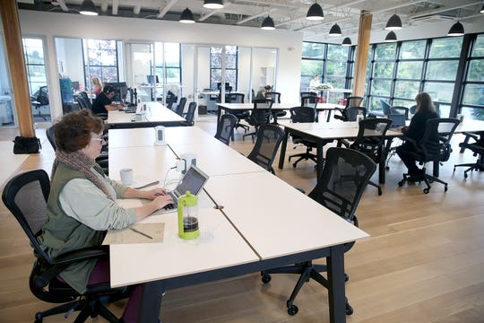 """Jennie Hoffman of Poulsbo works at a desk in Vibe Coworks in Poulsbo. The new Centennial building in Poulsbo, will soon be home to Vibe Coworks (coworking space), ChocMo (restaurant), High Spirits (""""destination"""" liquor store) and Crabtree Kitchen + Bar (restaurant)."""