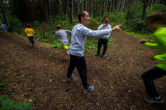 Essex XC coach Eric Langevin cues runners about when to start a drill at the Essex Tree Farm during a team practice on Monday. Oct. 1, 2018.