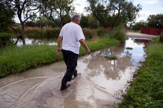 "Gus De La Pena walks through the water on his property in the Tierra Grande colonia on Monday, October 1, 2018 from recent rains. He has made efforts to secure his home by placing dirt around his home. At one time Nueces County received a grant for $5000,000 to improve drainage in the colonia and the plan was to run a drainage ditch to an adjacent drainage ditch a quarter of a mile away, said Lionel Lopez, founder of South Texas Colonia Initiative. ""But, they didn't do it,"" Lopez said. ""What they did was clean the ditches, mow the grass and I don't know what else they did. But, I know they didn't do what they were supposed to do."""