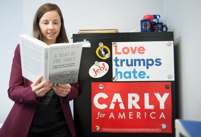 "Rutgers-Camden professor Kelly Dittmar, who co-wrote ""A Seat at the Table: Congresswomen's Perspective on Why Their Presence Matters,"" holds a copy of her book as she stands in her Camden office."
