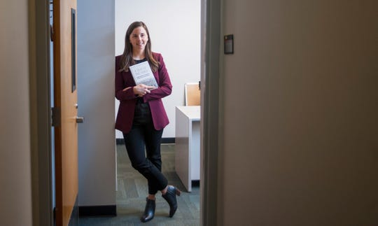 """Rutgers-Camden professor Kelly Dittmar, who co-wrote """"A Seat at the Table: Congresswomen's Perspective on Why Their Presence Matters"""",, holds a copy of her book as she stands in her Camden office."""
