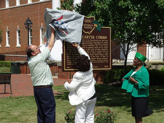 Ohio University Chillicothe Dean Martin Tuck, Rachel Foster and Gladys Turner Finney remove the covering from a historical marker for Joseph Carter Corbin outside Bennett Hall on the OU-C campus in 2017.