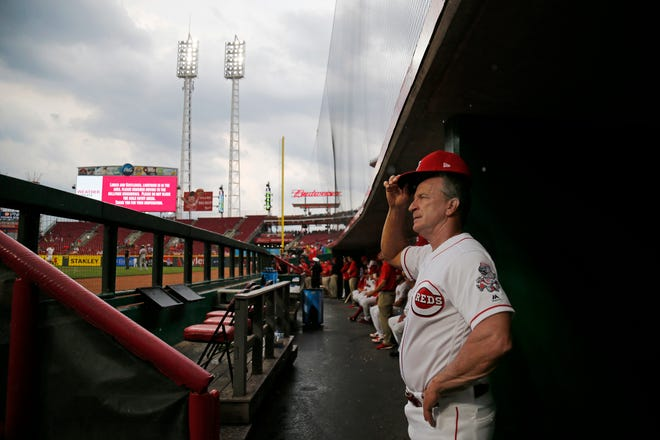 Cincinnati Reds interim manager Jim Riggleman (35) watches from the dugout as rain clouds roll in during the second inning of the MLB National League baseball game between the Cincinnati Reds and the St. Louis Cardinals at Great American Ball Park in downtown Cincinnati on Friday, June 8, 2018. The Reds trailed 2-1 after two innings.