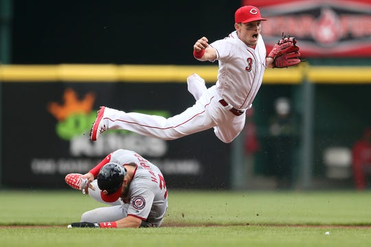 Nationals right fielder Bryce Harper (34) slides to break p a double play as Cincinnati Reds second baseman Scooter Gennett (3) throws to first base in the first inning of the Opening Day National League baseball game between the Washington Nationals and the Cincinnati Reds, Friday, March 30, 2018, at Great American Ball Park in Cincinnati.