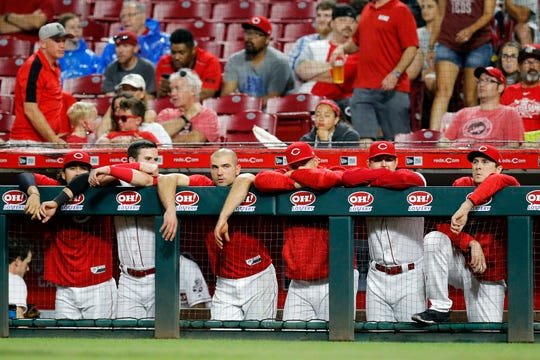The Cincinnati Reds bench watches from the dugout in the 10th inning of the MLB National League baseball game between the Cincinnati Reds and the St. Louis Cardinals at Great American Ball Park in downtown Cincinnati on Friday, June 8, 2018. The Reds lost 7-6 in 10 innings.