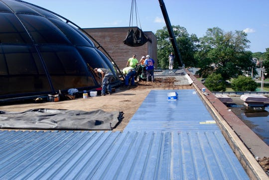 The roof being replaced next to the iconic dome of the LHS Academy of Science and Technology.