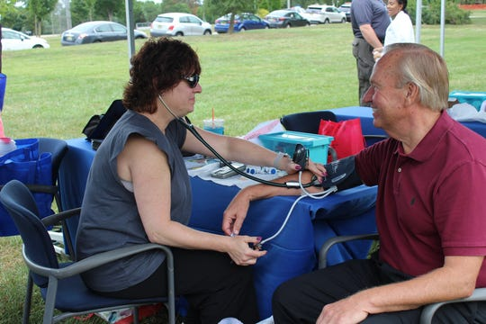 New Brunswick MayorJim Cahill(right) took advantage of the free health screenings offered by Saint Peter's University Hospital Community Health Services Department at Health and Play Family Day 2018 on Saturday, Sept. 8. Checking Cahill's blood pressure is  Stephanie Peluso-Riti, MSN, RN, CEN, FN-CSA. The event was held at Buccleuch Park and included complimentary blood pressure, blood sugar and cholesterol screenings and a variety of family-focused educational activities, games and more. The event was presented by Saint Peter's University Hospital and the New Brunswick Recreation Department, with support from PNC Bank and Rutgers University National Institute for Early Education Research.
