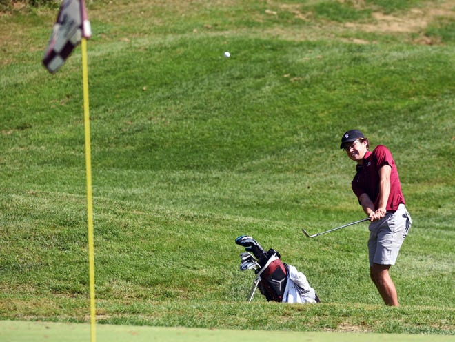 Jonah Hanes, of John Glenn, chips on to the 16th green during the Division II district golf tournament on Monday at EagleSticks.