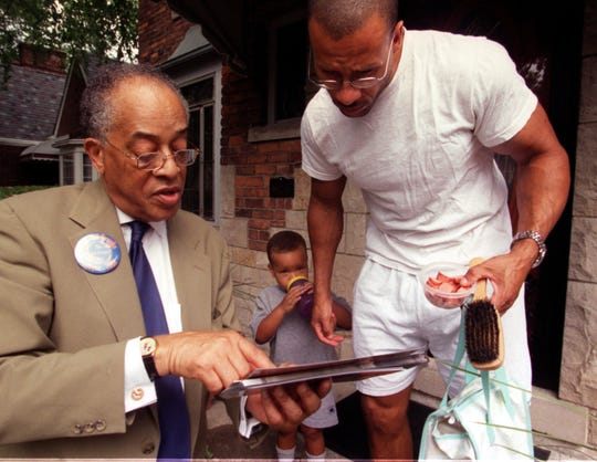 Detroit mayoral candidate Bill Brooks goes door-to-door in August 2001 on the east side of Detroit as he talks with Kevin Rigby Sr. about his issues, while Kevin Jr. listens.