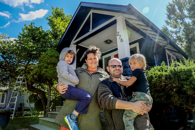 Nicole Seals, 44, holds her son David Seals III, 5, while standing with her husband David Seals Jr., 44, while he holds their son Steven Seals, 3, in front of their home in Clawson, Mich. on Saturday, Sept. 29, 2018.