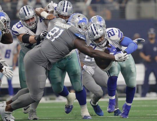 Detroit Lions defensive tackle A'Shawn Robinson tackles Dallas Cowboys running back Ezekiel Elliott in the first half in Arlington, Texas, Sunday, Sept. 30, 2018.