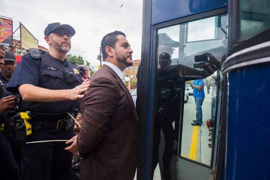 Abdul El-Sayed is escorted onto a waiting bus by police in handcuffs as he is arrested while protesting with members of 'Fight For $15' and striking McDonalds employees in front of McDonalds on Woodward Avenue Tuesday, Oct. 2, 2018.
