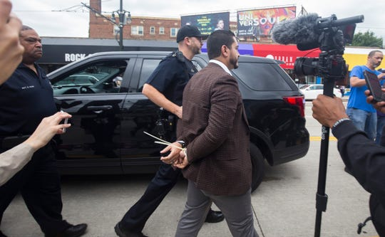 Abdul El-Sayed is escorted by police in handcuffs as he is arrested while protesting with members of 'Fight For $15' and striking McDonalds employees in front of McDonalds on Woodward Avenue Tuesday, Oct. 2, 2018.