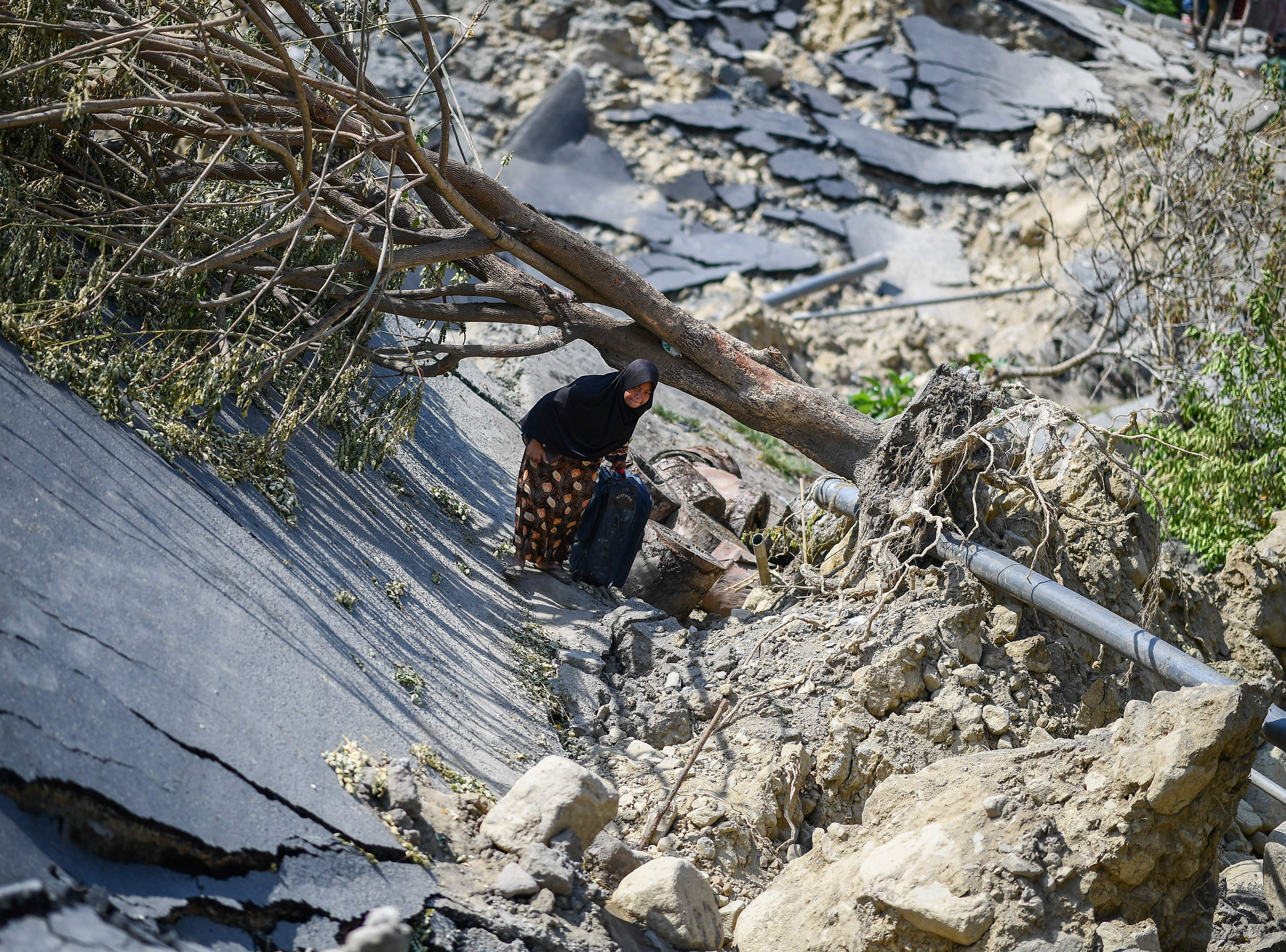 A woman drags a suitcase along a destroyed road in Palu, Indonesia's Central Sulawesi on Oct. 2, 2018, after an earthquake and tsunami hit the area on Sept. 28. The bodies of dozens of students have been pulled from their landslide-swamped church in Sulawesi, officials said, as an international effort to help nearly 200,000 Indonesia disaster victims ground into gear.