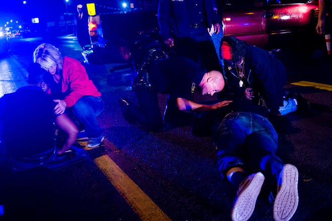 Injured protesters are examined after a burgundy Chevrolet pickup truck smashed into a protest fighting for a minimum wage increase Tuesday, Oct. 2, 2018, in Flint.