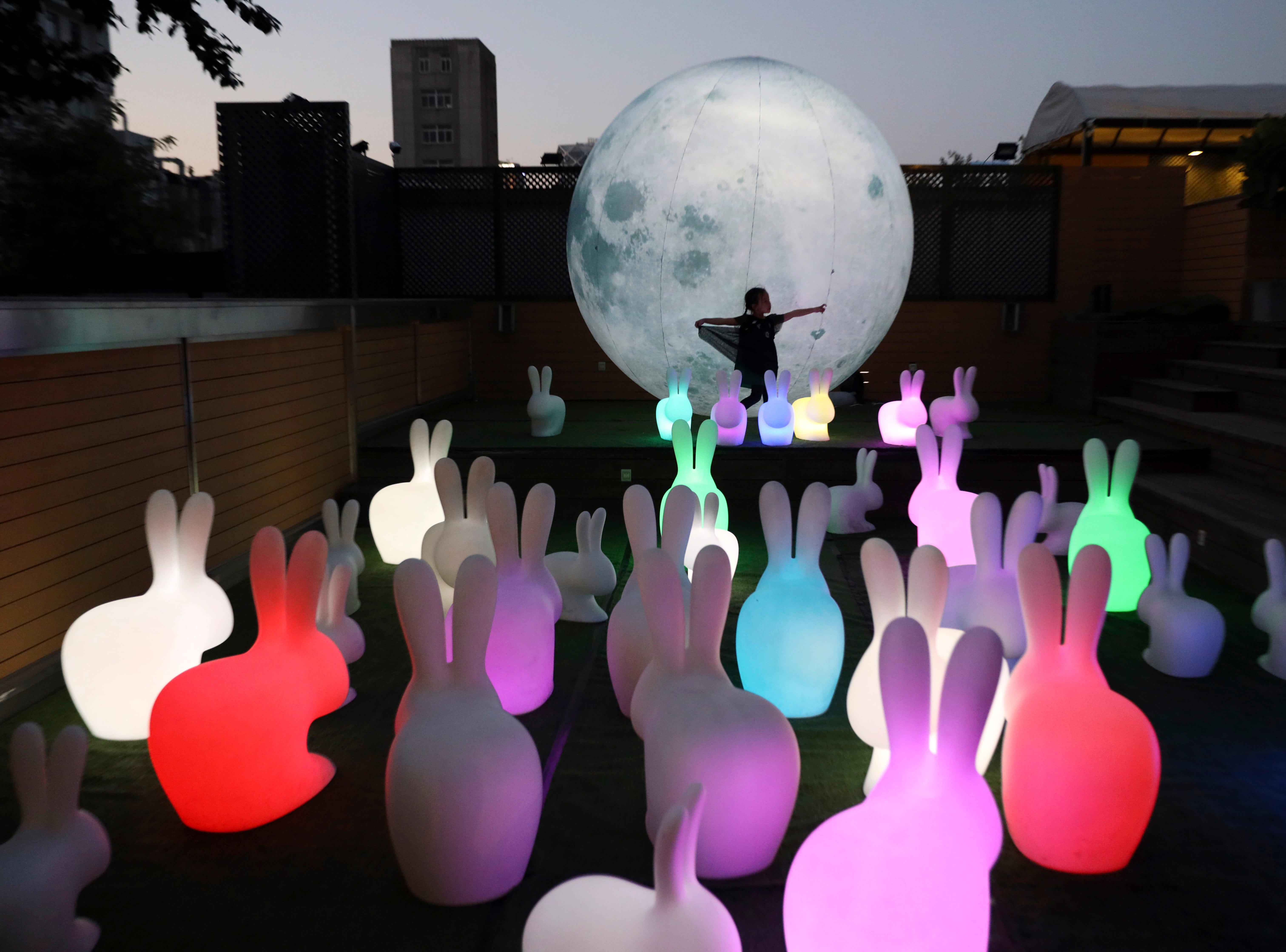 A dancing girl is silhouetted by a balloon moon installation at an art district in Beijing, China, Tuesday, Oct. 2, 2018. The installation art is part of a parent and child event coinciding with the Chinese National Day.