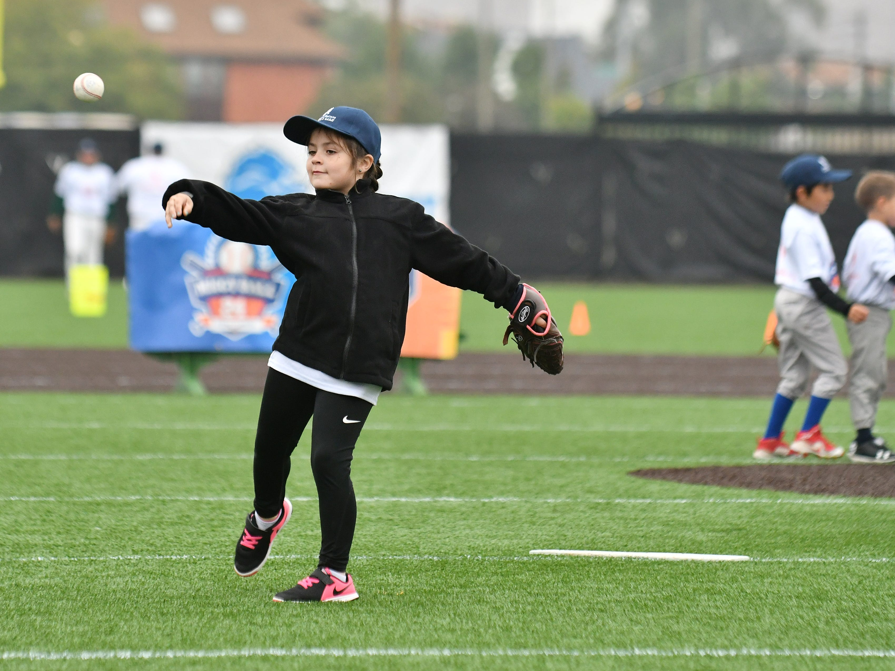 The only girl participant, Rosalie Plascencia, 7, of Detroit, throws a baseball in the pitching portion of the activities.
