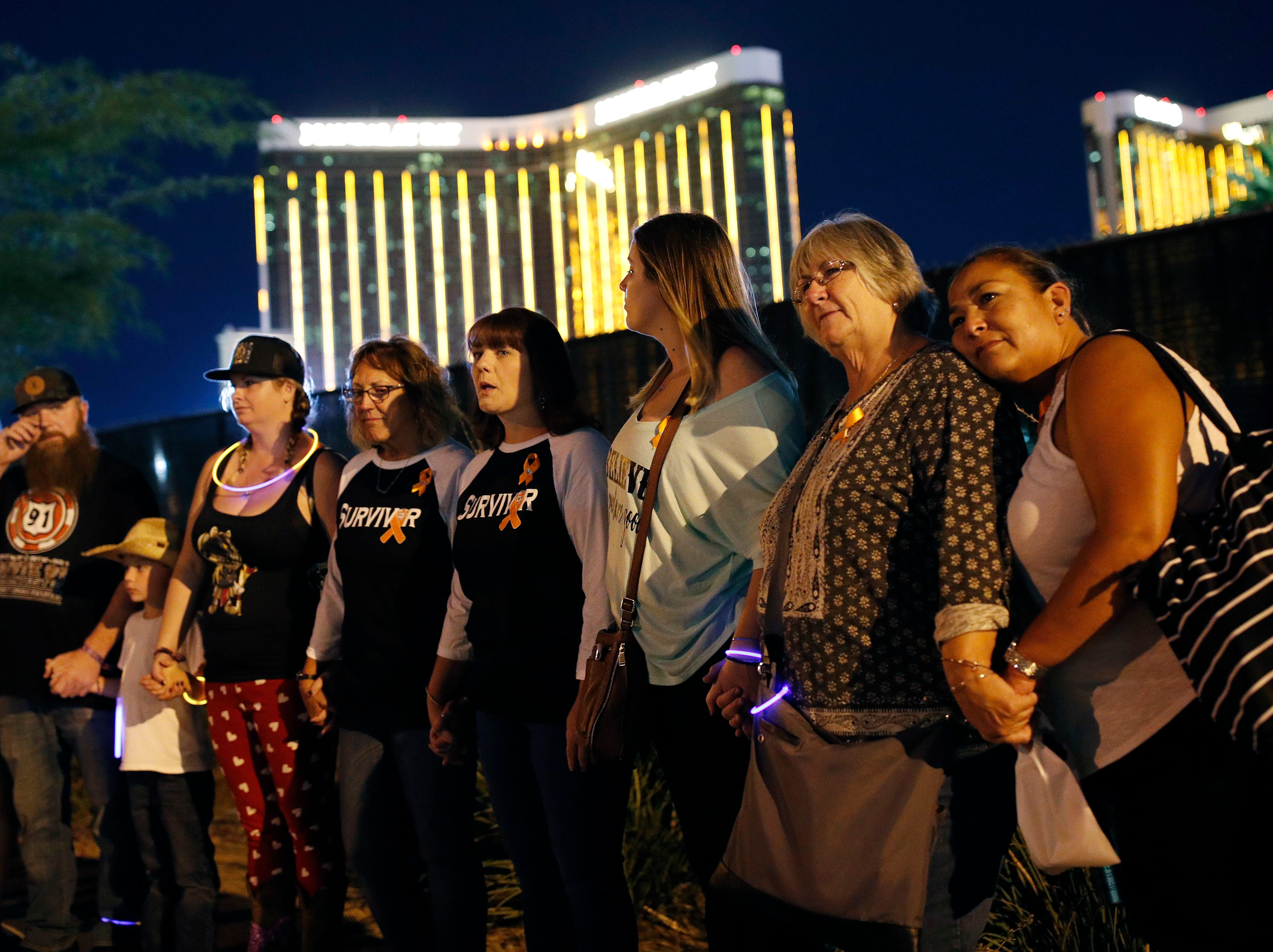Survivors of the mass shooting a year ago form a human chain around the shuttered site of a country music festival on Monday, Oct. 1, 2018, in Las Vegas. As people were linking arms and holding hands Monday night near the concert site, officials and several hundred others across town listened to bagpipes and the names of the 58 victims being read aloud.
