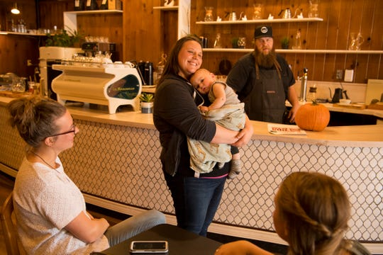 Tuck, fresh from a morning nap, comes out to greet customers with his mom, Kendra Rudibaugh, at White Swan Coffee Lab in W. Franklin Street Tuesday morning. Dad, David Rudibaugh, and mom were keeping the local business open from 8 a.m. - noon while the West Side Nut Club Fall Festival was in full swing.