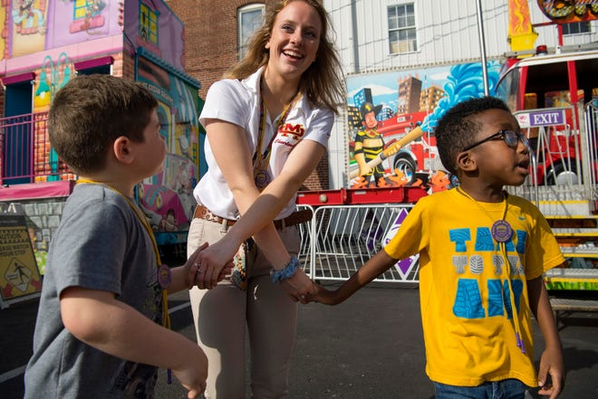 Sophie Lottes, 17, a senior at Mater Dei High School tries to keep up with her charges, Ryker Carnahan, 6, left, and Justice Eastwood, 7, right, at the Special Kids Day at the West Side Nut Club Fall Festival Tuesday morning. Lottes, a cheerleader, was volunteering to chaperone the youngsters at the festival.