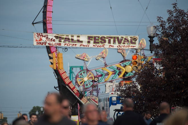 A sign advertising the Fall Festival hangs over the crowd at the intersection of 10th and Franklin Street Monday, Oct. 1, 2018.