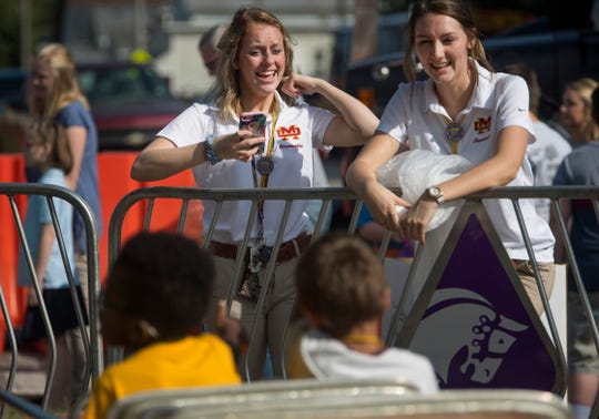 Mater Dei High School seniors Sophie Lottes, left, and Dani Humm, both 17, keep their charges company before their car ride at the West Side Nut Club Fall Festival Tuesday morning.