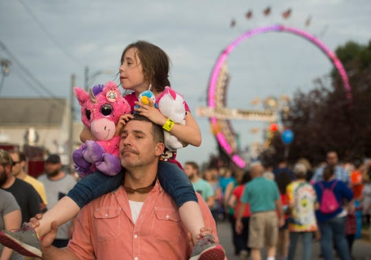 """Aspen and Gerald Miller stroll Franklin Street looking for food after playing games during the 2018 WSNC Fall Festival Monday, Oct. 1, 2018. Aspen said she spent all her quarters on a game to win a """"unicorn with wings."""""""