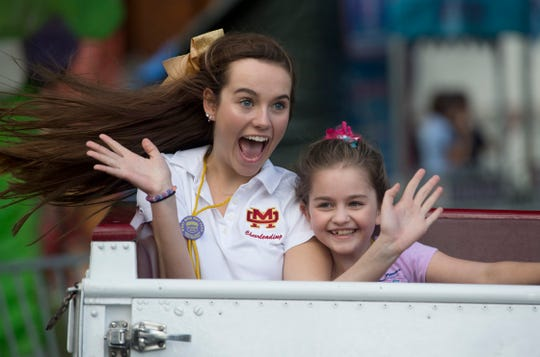Megan Sandwell, 16, a junior at Mater Dei High School, left, and Zoe Adams, a student in Hebron Elementary School's  Life Skills class, ride the Scrambler at the Special Kids Day at the West Side Nut Club Fall Festival Tuesday morning.