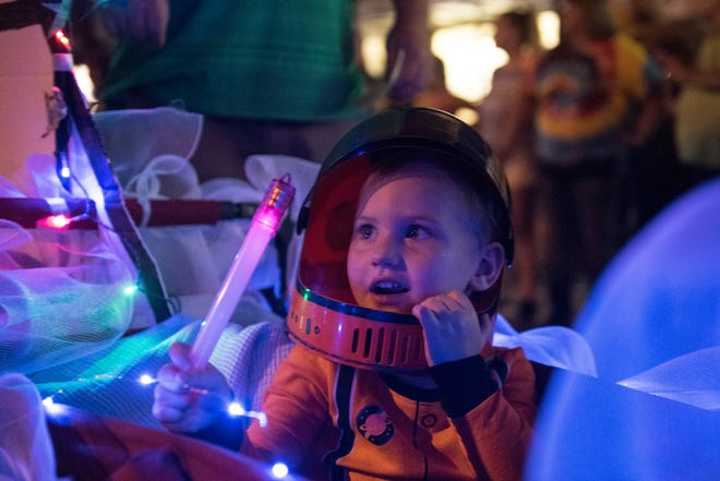 Lucy Mullis, 3, waves a glow stick while being carries on a NASA themed float during the 2018 WSNC Fall Festival Lighthouse Parade Monday, Oct 1, 2018.