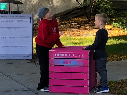 "Children play with one of the many pink benches created the ""Making Downtown Project."""