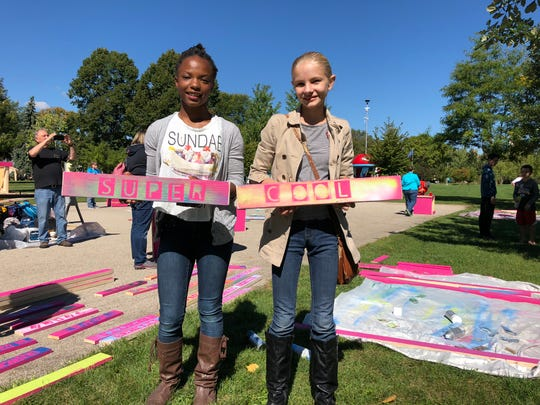 Participants in the event at Hamilton Park hold up the planks they designed for downtown benches.