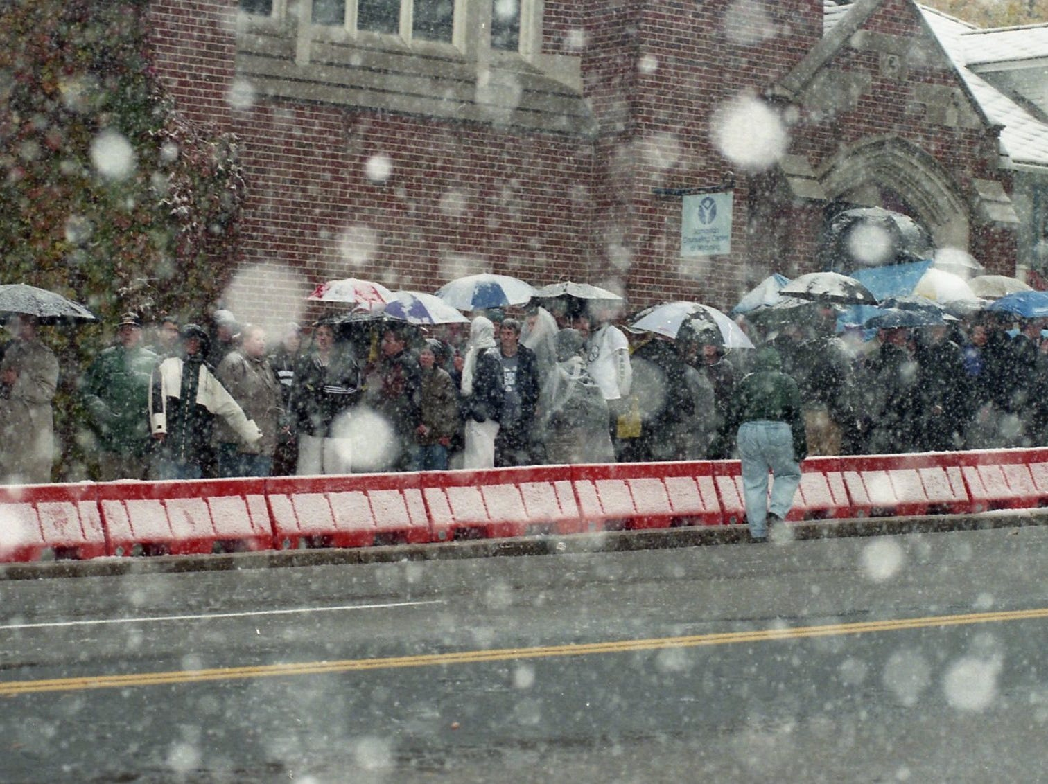 Funeral-goers stand outside in the snow (rain?) watiing to go into the church for the funeral service.