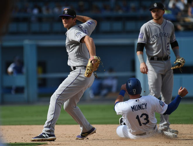October 1, 2018; Los Angeles, CA, USA; Colorado Rockies second baseman DJ LeMahieu (9) throws to first as Los Angeles Dodgers first baseman Max Muncy (13) slides into second during the seventh inning in the National League West division tiebreaker game at Dodger Stadium. Mandatory Credit: Richard Mackson-USA TODAY Sports