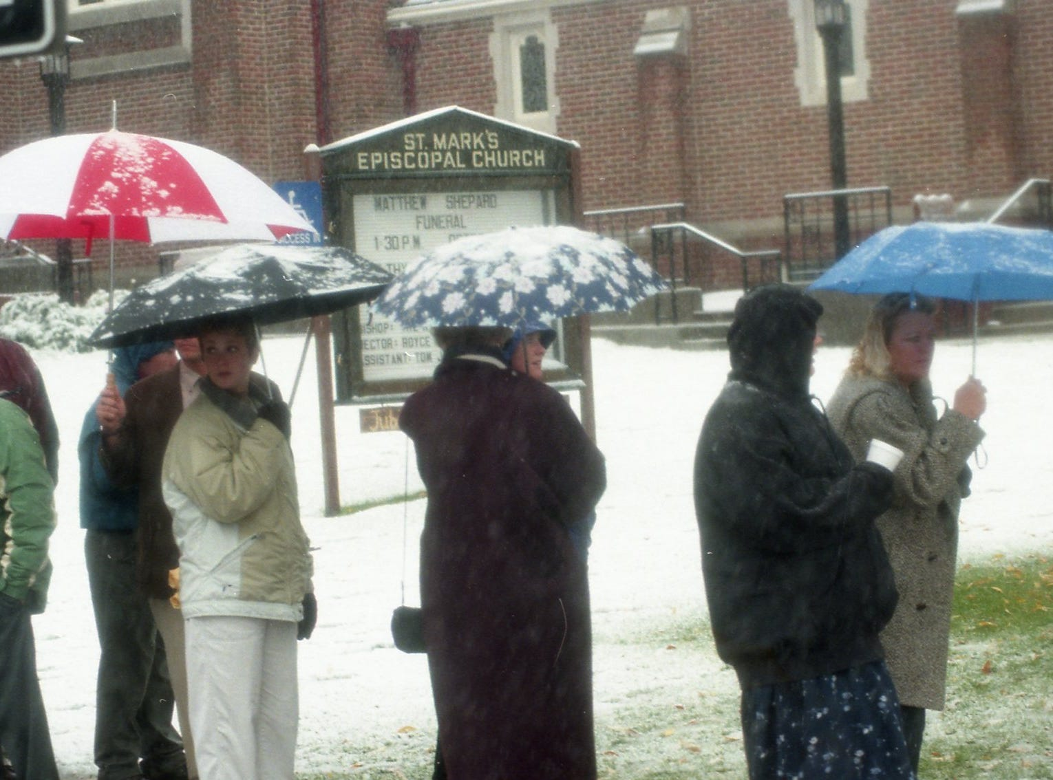 Individuals stand outside the church where Matthew Shepard's funeral was held.
