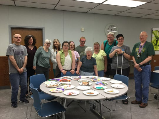 Workers at Algoma Mop Manufacturers with some of the paper plate collages they created with artist Melissa Dorn.