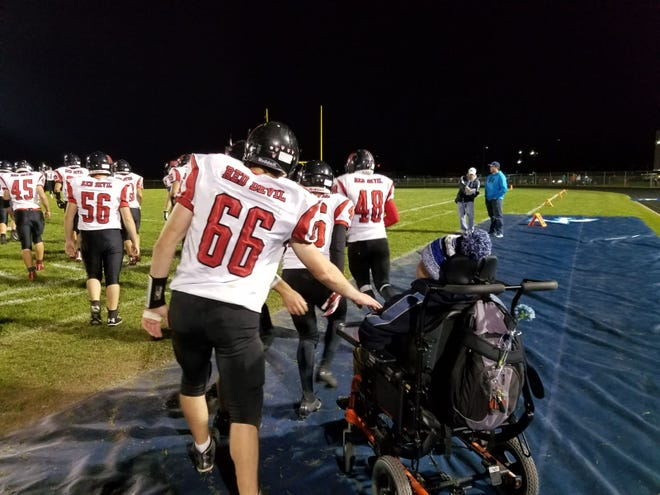 Green Bay East football player Austin Dewberry (66) gives Little Chute water boy Raymond Beecher a fist bump after Little Chute's 42-0 win on Friday.