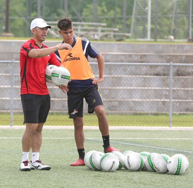Dominic Gadia, the Guam Football Association's coach education development officer, left, provides some coaching points during a practical session run by Morgan McKenna during the GFA Skill Acquisition Coaching Course, which concluded Sept. 30 at the Guam Football Association National Training Center.