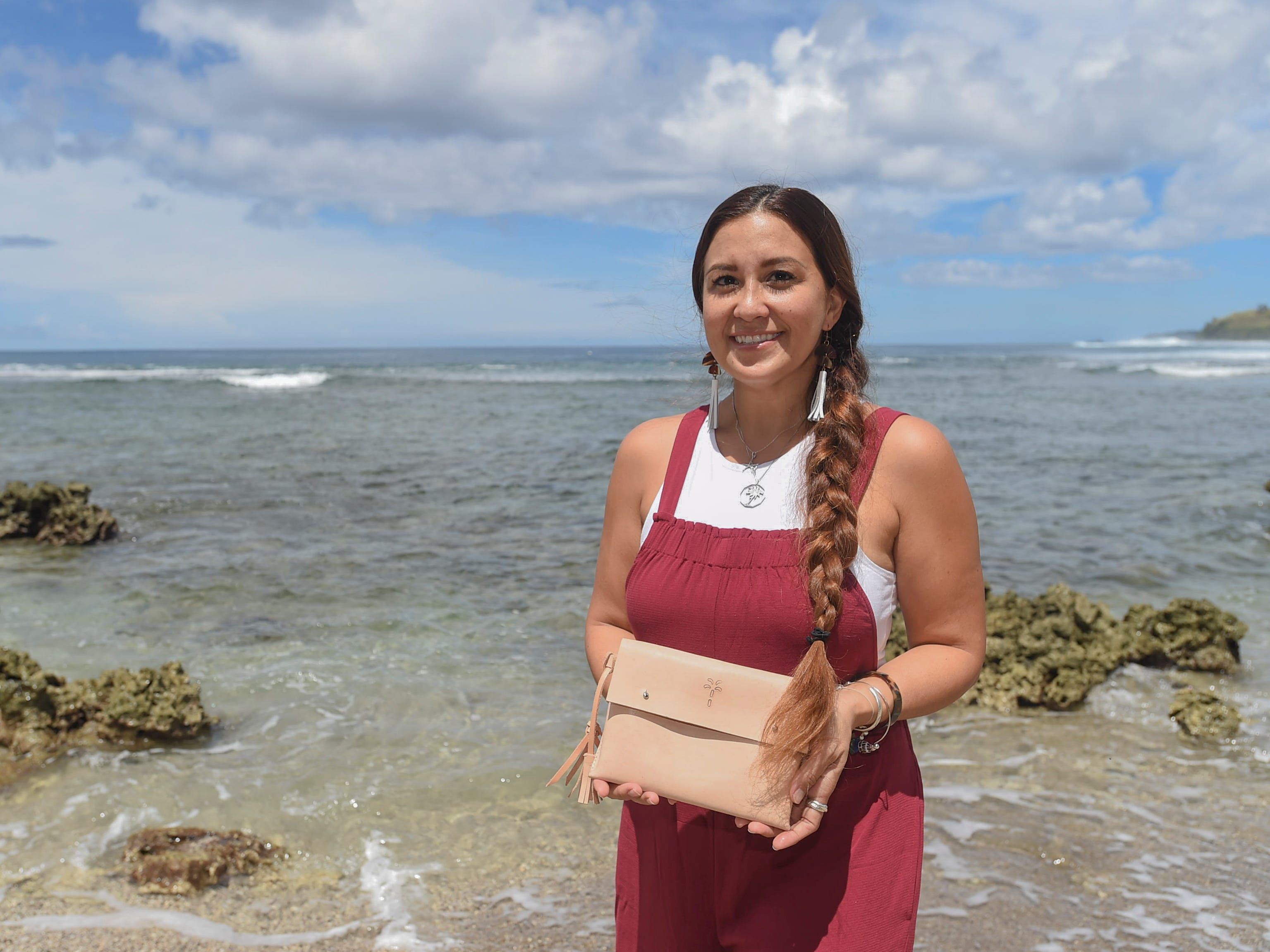 The Blue Latitude owner Abby Crain displays her handcrafted leather clutch in Merizo on Oct. 2, 2018.