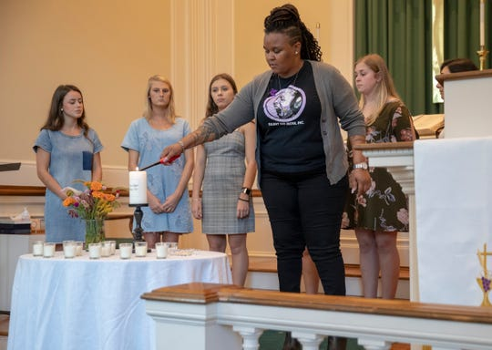 Danyette Smith, lights a candle during a ceremony to recognize survivors of domestic violence and the lives that it has taken in central Indiana, Meridian Street United Methodist Church, Indianapolis, Tuesday, Oct. 2, 2018. October is Domestic Violence Awareness Month, and from the period of time from July 1, 2017 to June 30 of this year, 8 people in Marion County, and 11 in central Indiana lost their lives as a result of domestic violence.