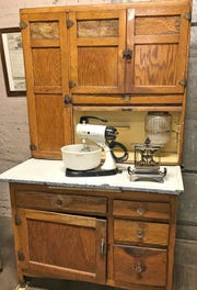 This Sellers Hoosier cabinet was manufactured in Elwood, Indiana and features a porcelein work surface.