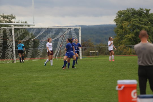 Teammates congratulate Morgan Boerman after she scored a goal.