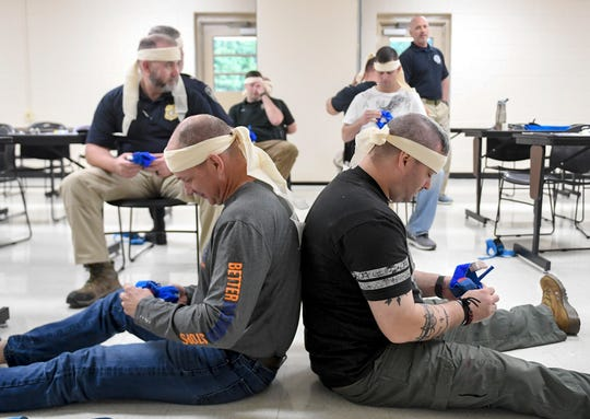 Joe Lambert and Rick Finley prepare tourniquets to wrap around their arms while blindfolded during the Tactical Medical for First Responders training, Tuesday, October 2.