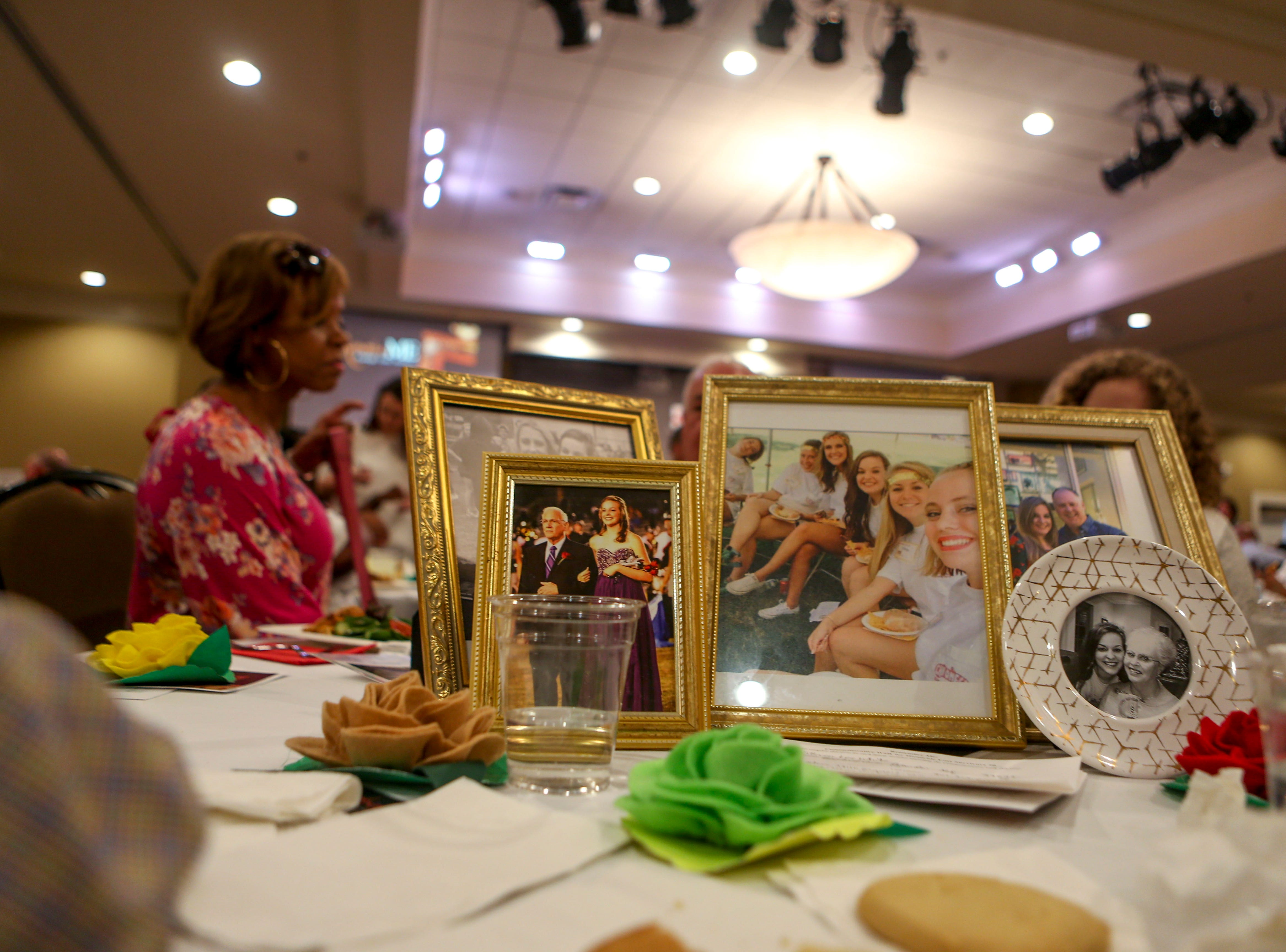 Photos to memorialize a victim of suicide are placed at the center of a table during the annual Remember Me Walk hosted at Union University in Jackson, Tenn., on Monday, Oct. 1, 2018.