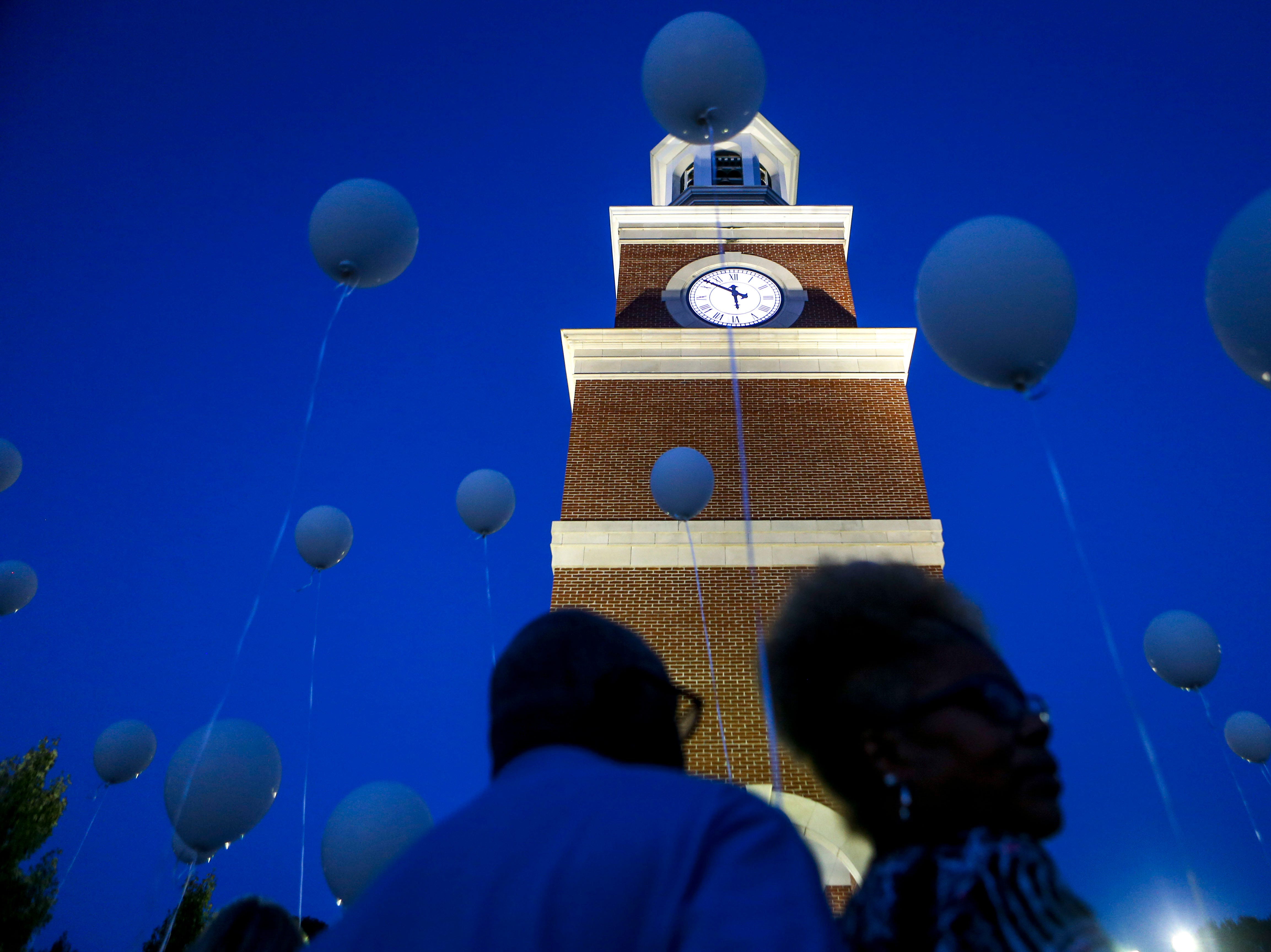 Attendees gather at the base of the clock tower before releasing balloons into the sky during the annual Remember Me Walk hosted at Union University in Jackson, Tenn., on Monday, Oct. 1, 2018.