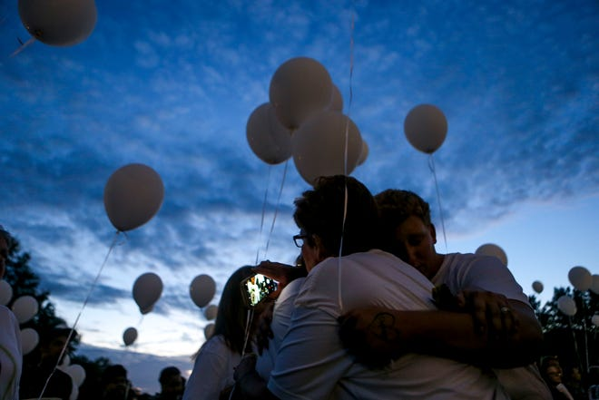 A family embraces one another before releasing balloons during the annual Remember Me Walk hosted at Union University in Jackson, Tenn., on Monday, Oct. 1, 2018.
