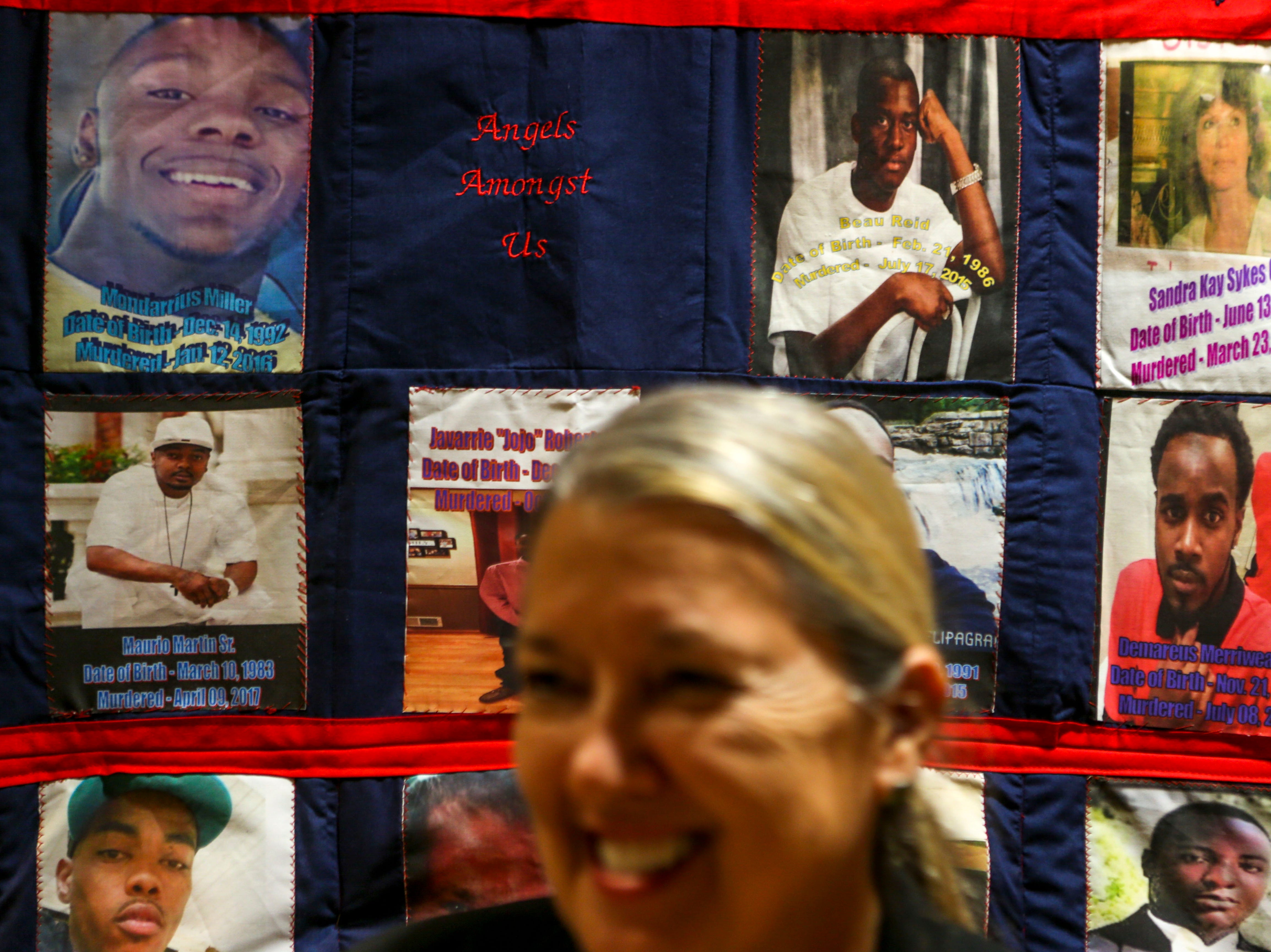 Nita Mehr, associate dean of the school of social work at Union University, speaks in front of a quilt made with photos of victims of violence during the annual Remember Me Walk hosted at Union University in Jackson, Tenn., on Monday, Oct. 1, 2018.