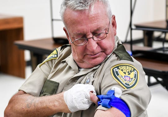 Robert Hitchborn wraps a tourniquet around his arm with his right hand which is limited to one finger during the Tactical Medical for First Responders training, Tuesday, October 2.