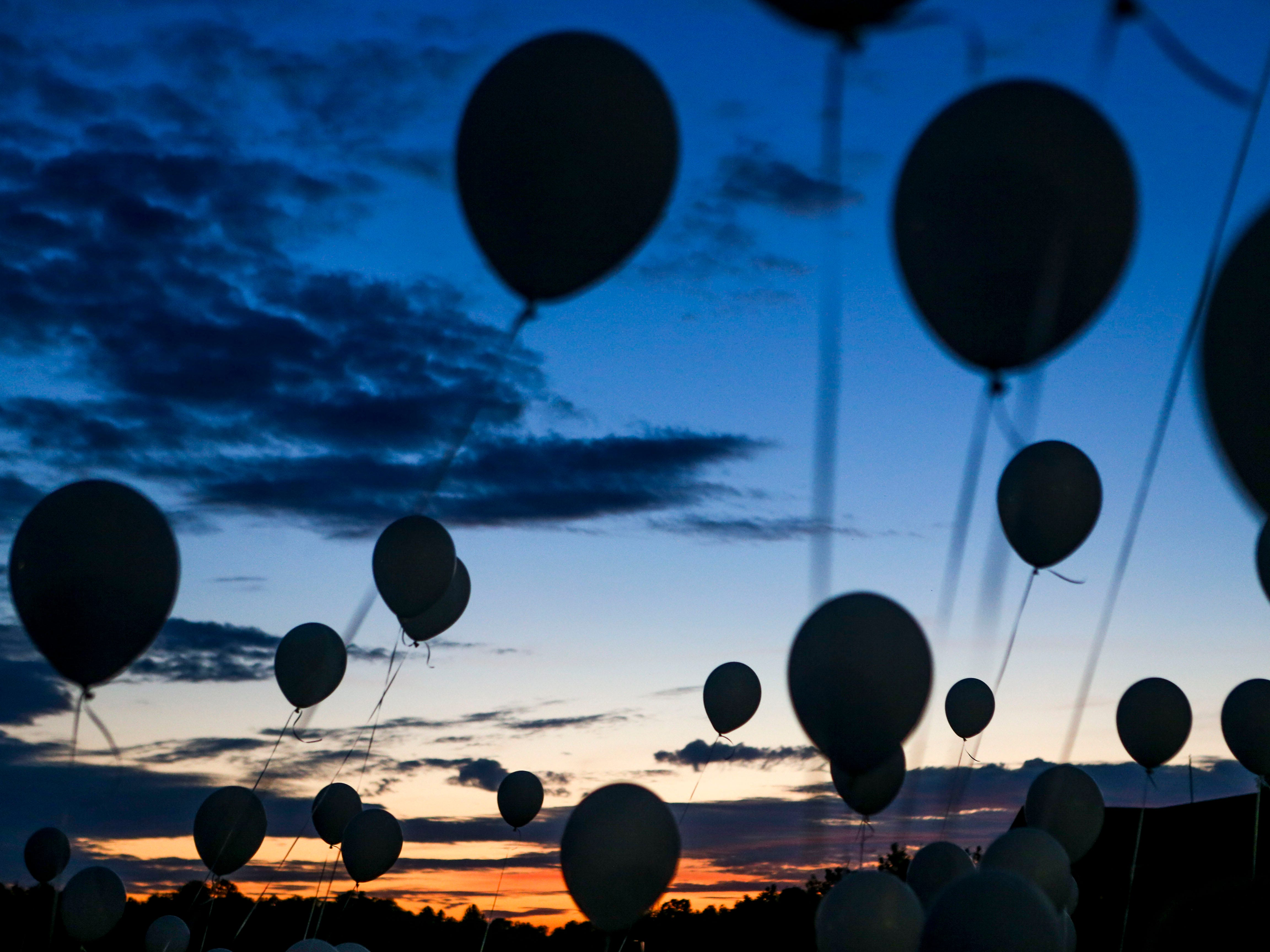 Balloons held by attendees cover the sunset during the annual Remember Me Walk hosted at Union University in Jackson, Tenn., on Monday, Oct. 1, 2018.
